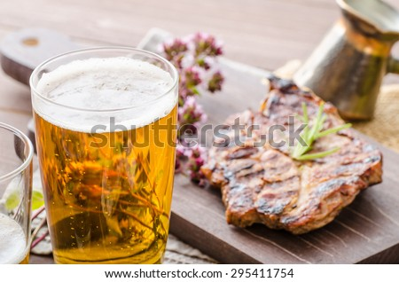 Grilled pork meat with beer, garlic dip, roasted potatoes, tomatoes and fried egg - stock photo