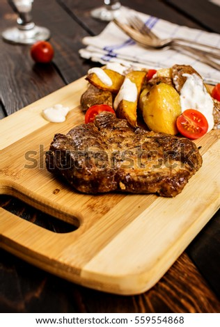 Grilled pork neck steak with potatoes on wood table
