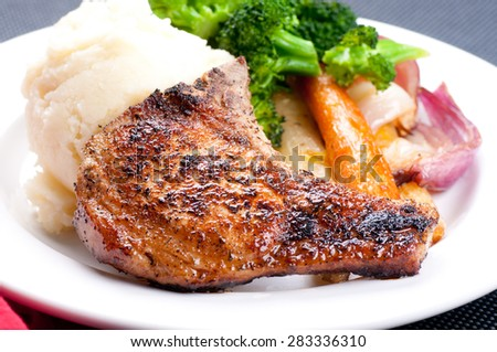 grilled pork rib chop with mashed potato and roasted carrot