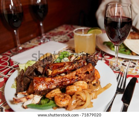 Grilled pork ribs and shrimps with cocktail and wine - stock photo