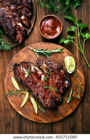 Grilled pork ribs, tomato sauce and green herbs on wooden background, top view - stock photo