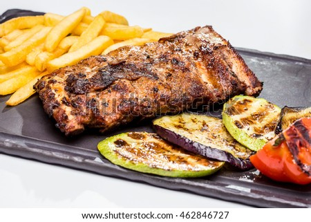 Grilled pork ribs with fries and vegetables. on the board of stones and a white background