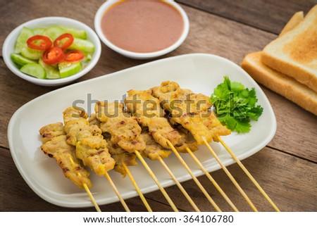 Grilled pork satay with peanut sauce and toast, Thai food - stock photo