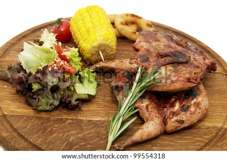 Grilled quail, and fresh herbs on a wooden plate - stock photo
