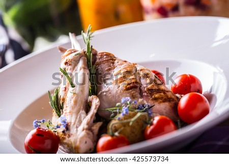 Grilled rabbit leg with rosemary and vegetable decoration. - stock photo