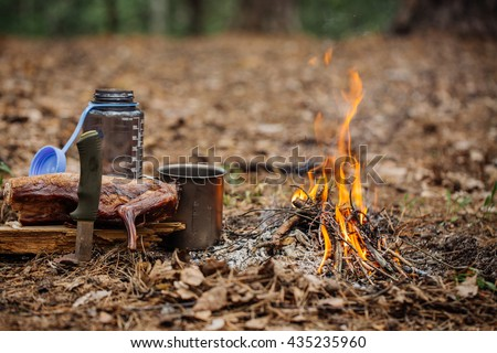 grilled rabbit meat on wooden board, with knife, water bottle and titanium mug near the fire outdoors. bushcraft, adventure, travel, tourism and camping concept. - stock photo