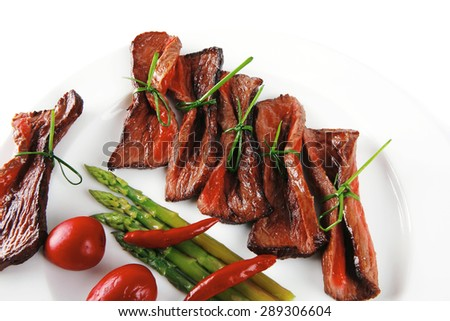 grilled red beef meat rolls with asparagus and hot spices on china plate isolated over white background - stock photo