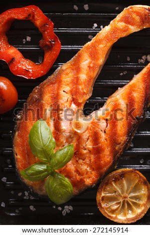 Grilled red fish steak salmon and vegetables on the grill pan. vertical top view close-up  - stock photo