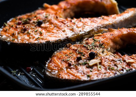 Grilled red fish steak salmon on the grill pan, closeup view - stock photo