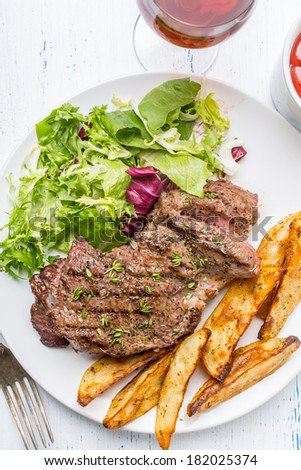 Grilled Rib-eye Beef Steak with Green Salad and Herb Potato Wedges - stock photo