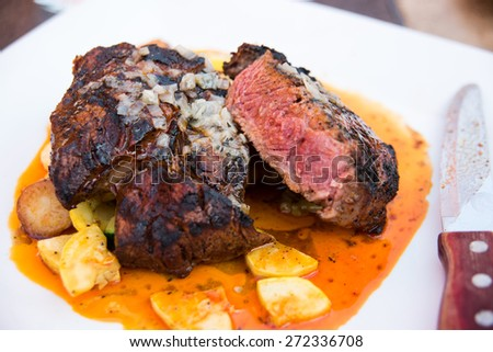 Grilled Rib Eye Steak Served with Zucchini and Potatoes - stock photo
