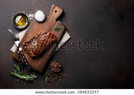 Grilled ribeye beef steak, herbs and spices. Top view with copy space for your text