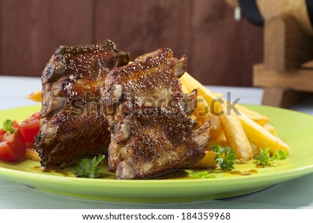 Grilled ribs on plate, served with fries