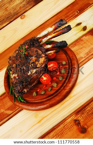 grilled ribs on wooden table with vegetables - stock photo
