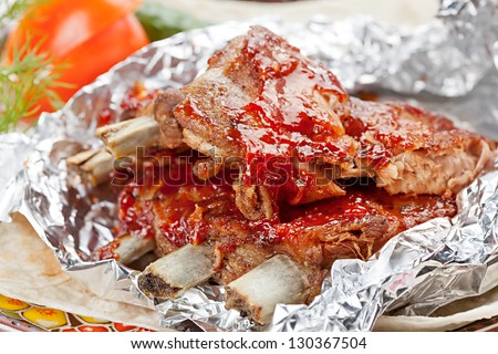 Grilled  ribs with vegetables and sauce on the plate covered in aluminum foil - stock photo