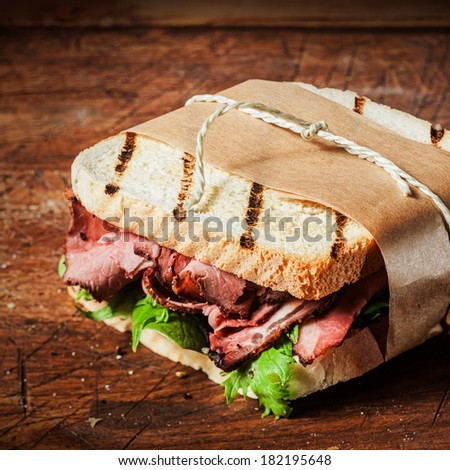 Grilled roast beef ,spinach and rocket sandwich tied in a brown paper takeaway wrapper - stock photo