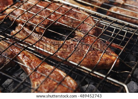 grilled roast meat lamb ribs on barbecue grid over charcoal
