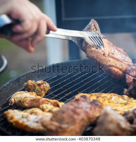 Grilled roasted juicy lamb steaks on cooking on barbecue, outside