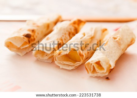 Grilled rolls of bread lavash with cheese suluguni - stock photo