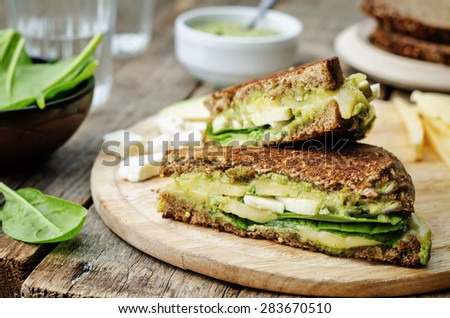 grilled rye sandwiches with cheese, spinach, pesto, avocado and goat cheese. the toning. selective focus - stock photo