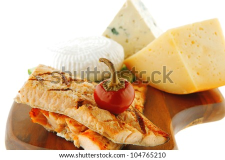 grilled salmon and french cheeses on wooden plate