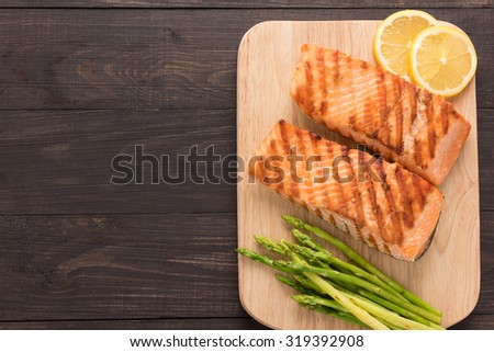 Grilled salmon and lemon, asparagus on the wooden background. - stock photo