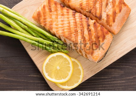 Grilled salmon and lemon, asparagus, on the wooden table. - stock photo