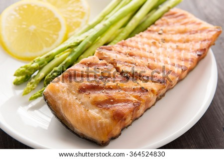 Grilled salmon and lemon; asparagus; on the wooden table.