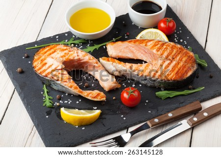 Grilled salmon and spices on stone plate over wooden table - stock photo