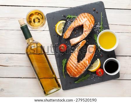 Grilled salmon and white wine on wooden table. Top view  - stock photo