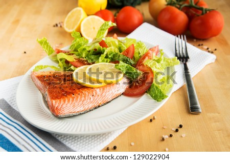Grilled Salmon Filet Served with Tomatoes and Romaine Salad - stock photo