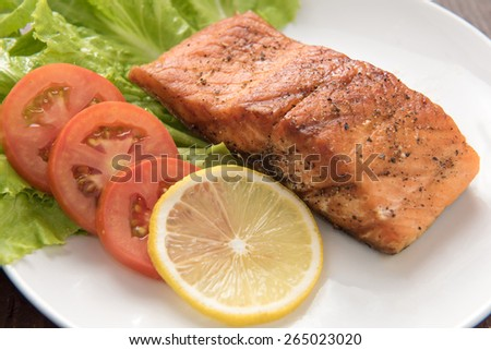 Grilled salmon fillet cooked BBQ and served with fresh herbs and lemon - stock photo