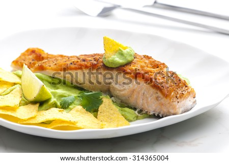 grilled salmon fillet with avocado sauce and nachos - stock photo