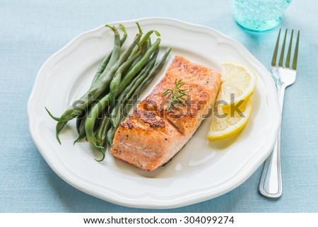 Grilled salmon fillet with green beans and lemon on white plate - stock photo