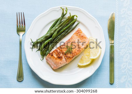 Grilled salmon fillet with green beans and lemon on white plate from above - stock photo