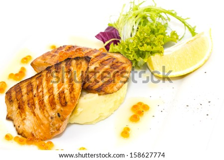 Grilled salmon fillet with vegetables and caviar
