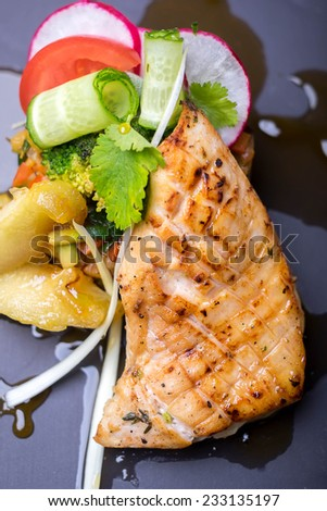 Grilled salmon fish fillet steak with vegetable salad, radish, tomato, cucumber on a serving board
