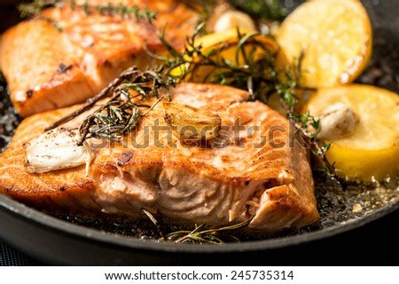 Grilled salmon fish with herbs, garlic and lemon. Closeup, selective focus
