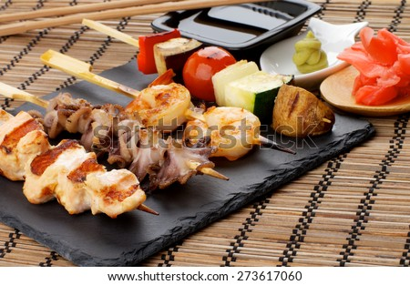 Grilled Salmon, Octopuses, Shrimps and Vegetables on Wooden Stick with Ginger, Soy Sauce and Wasabi closeup on Straw Mat background - stock photo