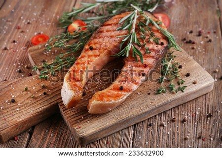 Grilled salmon on cutting board on wooden background - stock photo