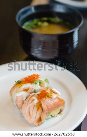 grilled salmon roll sushi with shrimp egg on top in white dish served with miso soup - stock photo