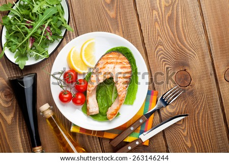 Grilled salmon, salad and condiments on wooden table. Top view with copy space - stock photo