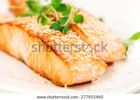 Grilled salmon, sesame seeds  and marjoram on white plate. Studio shot - stock photo