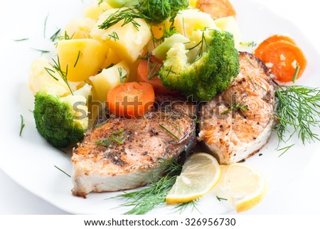 Grilled salmon steak garnished with vegetables at white. Closeup, selective focus.