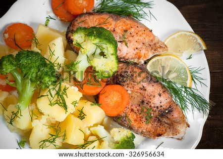 Grilled salmon steak garnished with vegetables. Closeup.