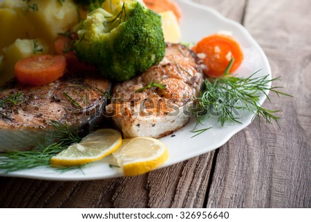 Grilled salmon steak garnished with vegetables. Closeup, selective focus. - stock photo