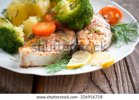 Grilled salmon steak garnished with vegetables. Closeup, selective focus.