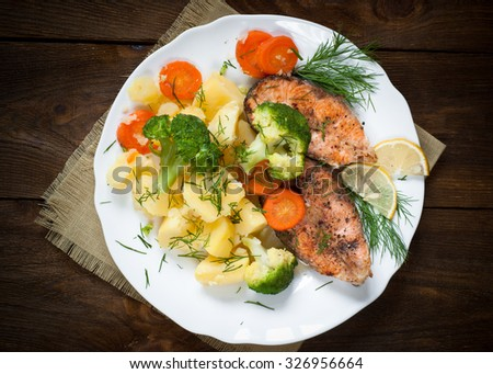 Grilled salmon steak garnished with vegetables. Top view. - stock photo