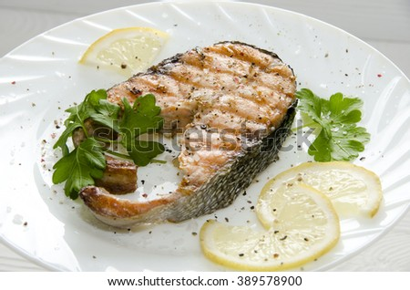 grilled salmon steak on a round white plate on a white wooden background with lemon parsley and spices - stock photo