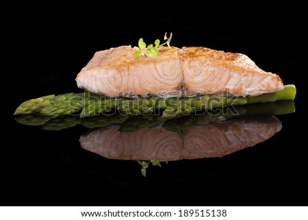 Grilled salmon steak on asparagus isolated on black background. Culinary seafood eating.  - stock photo